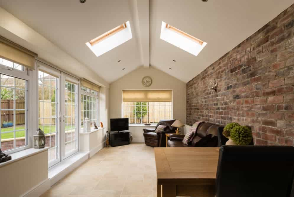 Modern Sunroom or conservatory extending into the garden with a featured brick wall